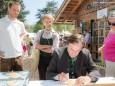 Franz Voves verziert ein Lebkuchenherz am Pirker Stand - Steiermark Frühling 2015 in Wien am Rathausplatz