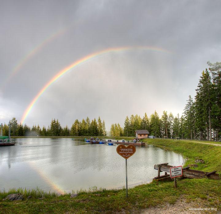 Bergwelle mit Regenbogen Spiegelung im See
